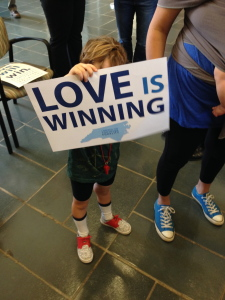 "Little Boy holding sign reading, ""Love is winning"""
